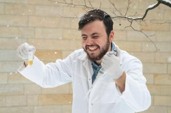 Man in white coat laughing in the snow