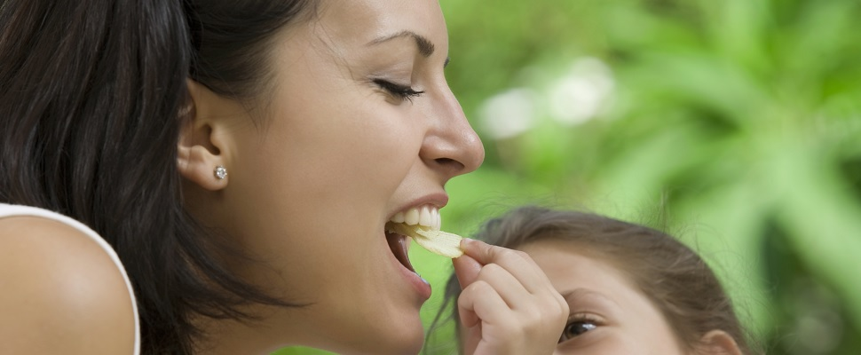 A child puts a piece of apple into a grown-up's mouth