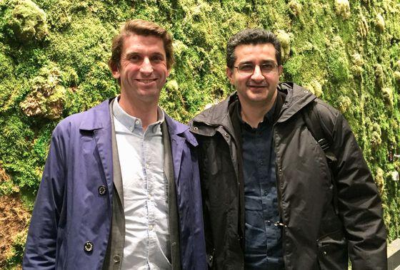 To menn står oppstilt foran kamera og smiler