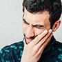 Bildet viser en mann som holder seg til kjeven mens ansiktsuttrykket hans uttrykker smerte.
