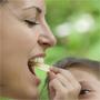 Et barn gir en eplebit til voksen i munnen