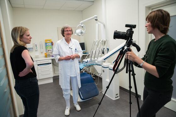 En kvinne i klinikktøy står i et tannlege-behandlingsrom og snakker med to kvinner, den ene bak et kamera.