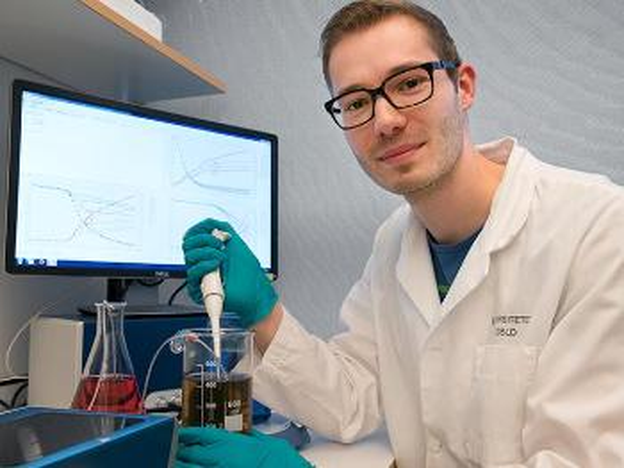 Foto av doktoranden som sitter i en lab med labfrakk foran instrumentene sine.