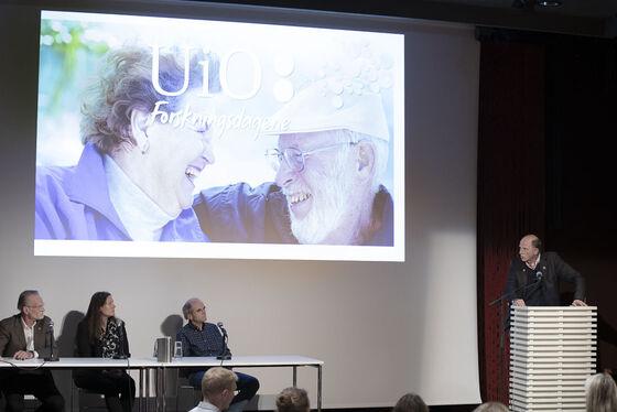 Tre deltakere sittende i panelsamtale og en person på talerstolen