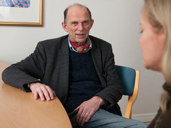 Foto av dekanen som sitter ved et bord og snakker med en dame.