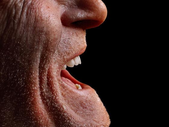 nærbilde av en eldre manns smilende munn.