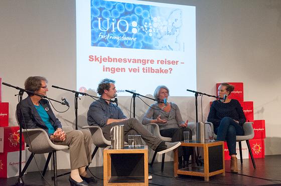 Bilde av fire forskere som sitter i lenestoler på et podium, med mikrofoner foran seg og bak dem på veggen er tittelen på arrangementet projisert: Skjebnesvangre reiser - ingen vei tilbake?