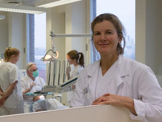 Foto av den nye studiedekanen som står oppstilt til høyre i bildet, smilende, foran en gruppe studenter samlet rundt en tannlegestol med pasient i, i en læringssituasjon i bakgrunnen.