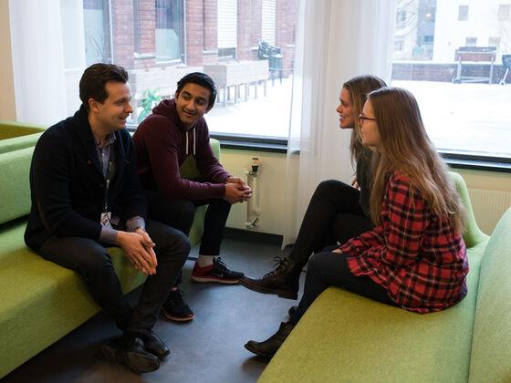 Foto av studiedekanen som sitter i en sofagruppe og prater sammen med tre studenter.