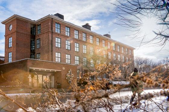 Utendørs bilde av et av byggene til Det odontologiske fakultet, et rødt, gammelt mursteinsbygg.
