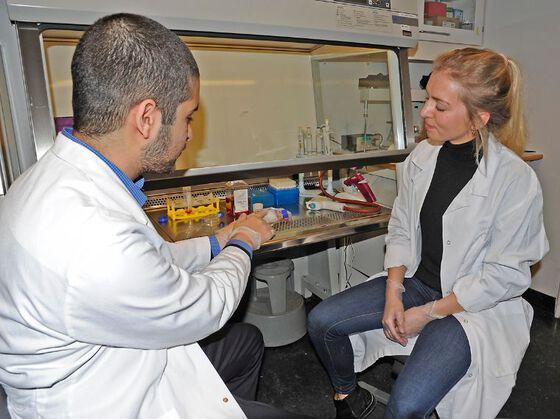 De to studentene sitter med lab-frakker foran en laboratorie-benk med mange instrumenter, og viser noe til hverandre.