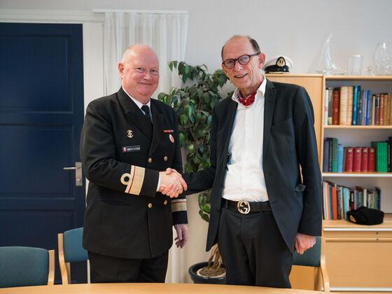 Bilde av kontreadmiralen og dekanen som håndhilser inne på et kontor, mens de ser inn i kamera