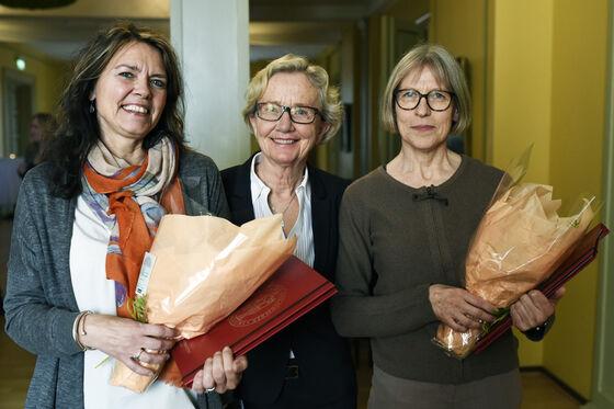 Foto av tre damer som står og smiler, de to ytterste holder hver sin blomsterbukett.