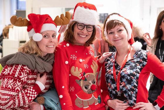 Tre kvinner i røde julegensere og nisseluer smiler til kamera