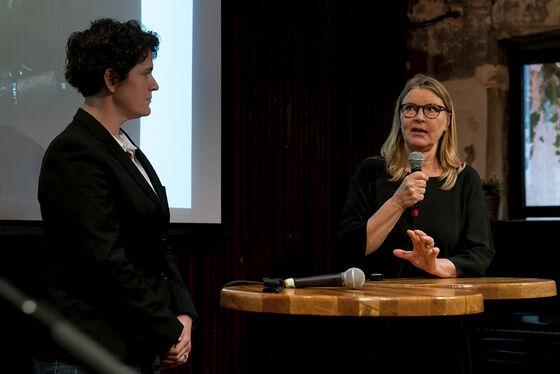 En dame med lyst hår snakker i en mikrofon til høyre. Til venstre står en dame og ser på hun som snakker.
