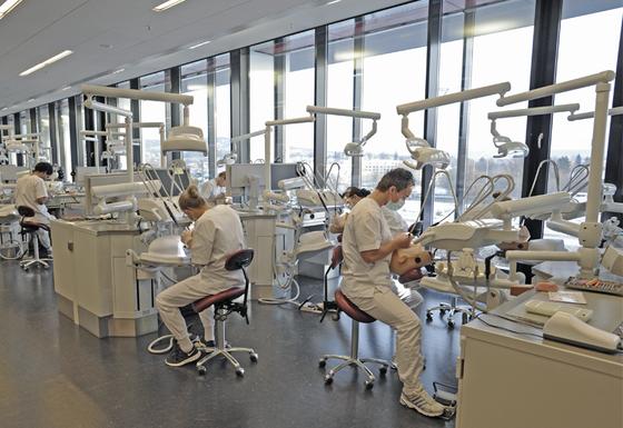 Ein sal med mange tannlegestolar og studentar som sit ved stolane og øver