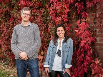 The two scientists looking happy outside, in front of a bright, autumn red hedge