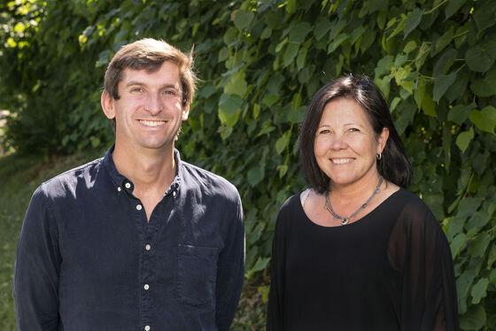 Halvnært profilbilde av to forskere som smiler til kamera foran en vegg av blader.