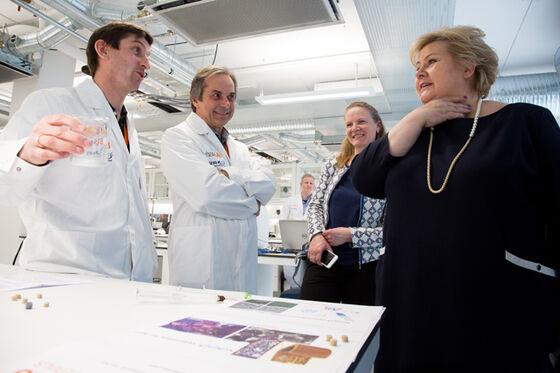 To menn i hvite lab-frakker forklarer noe til statsministeren til høyre, inne på en lab