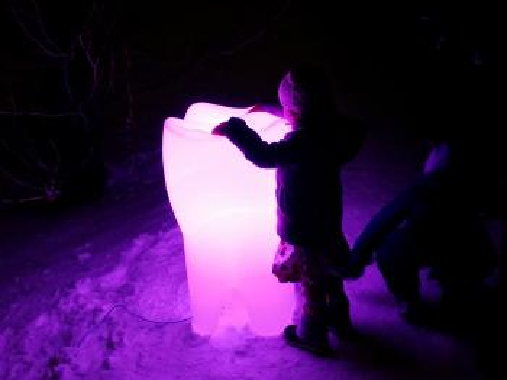 Et barn står og holder oppå en plasttann like stor som barnet, som lyser opp i rosa
