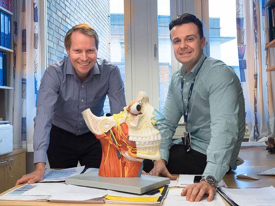Bilde av de to forskerne som smiler. De sitter bak en pult, med en modell av et menneskedhode med kjeve og hals eksoponert på pulten.