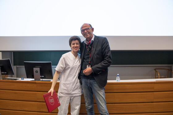 Bilde av prisvinneren som står og smiler til kamera med et diplom i hånden, sammen med dekanen.