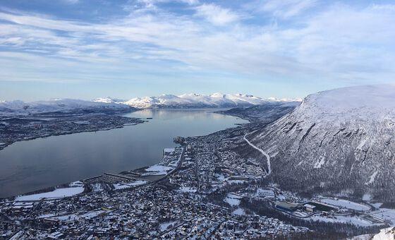 Oversiktsbilde av Tromsø by, liggende inntil en fjord, med fjell på den andre siden.