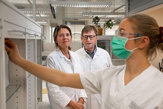 Bilde av en student som henter utstyr og to personer som ser på.