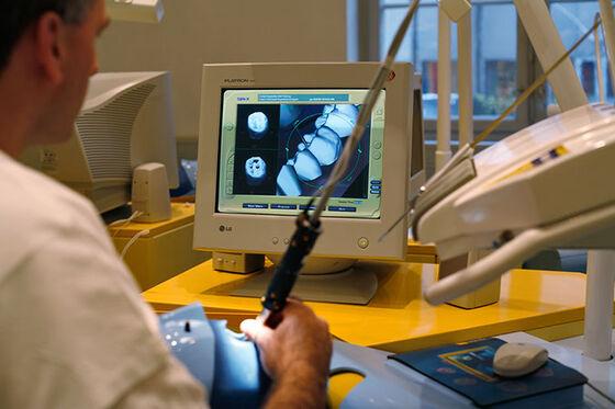 Foto av en mann som sitter med et instrument foran en dataskjerm. På skjermen vises grafiske bilder av tenner.